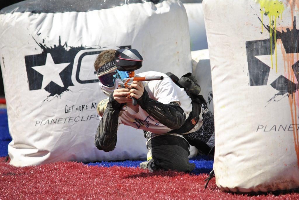 Image d'une personne jouant au paintball, avec une combinaison, une lanceur, un gun de paintball.
