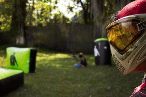 Sur cette image on peut observer un joueur de paintball avec un masque de paintball. Derrière on voit un terrain de paintball